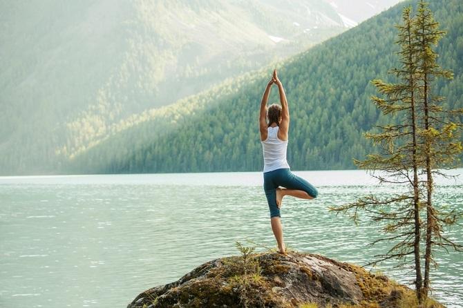Une femme fait du yoga face à un lac