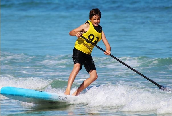 Un enfant faisant du stand-up paddle